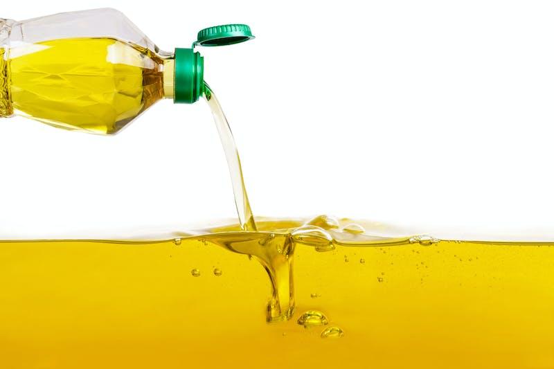 Vegetable oil pouring on vegetable oil background