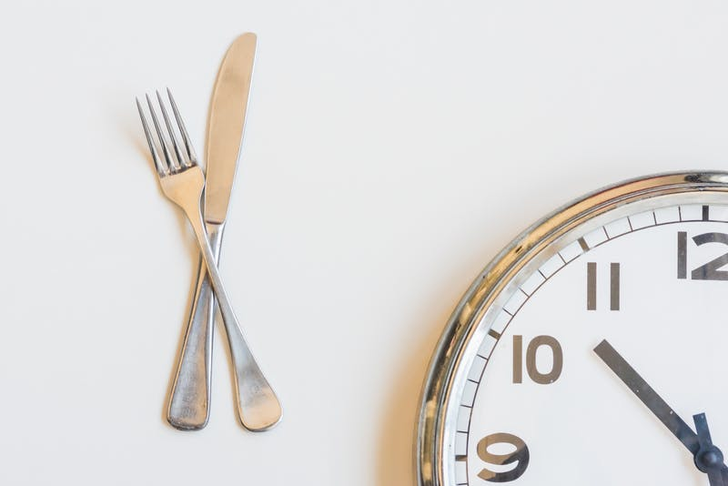 Knife and fork with clock on white background