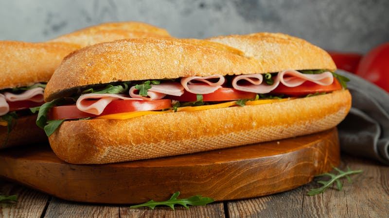 Two Long baguette Sandwiches with arugula, slices of fresh tomatoes, ham and cheese