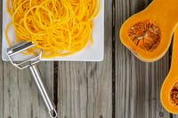 Overhead top view of freshly peeled butternut squash noodles and julienne peeler. Wooden background and white plate for fresh natural vegetable noodle pasta. Vegan, gluten free, low carb health food.