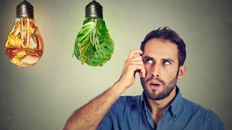 man thinking looking up at junk food green vegetables