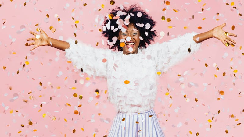 Happy young woman celebrating with arms out and lots of falling confetti