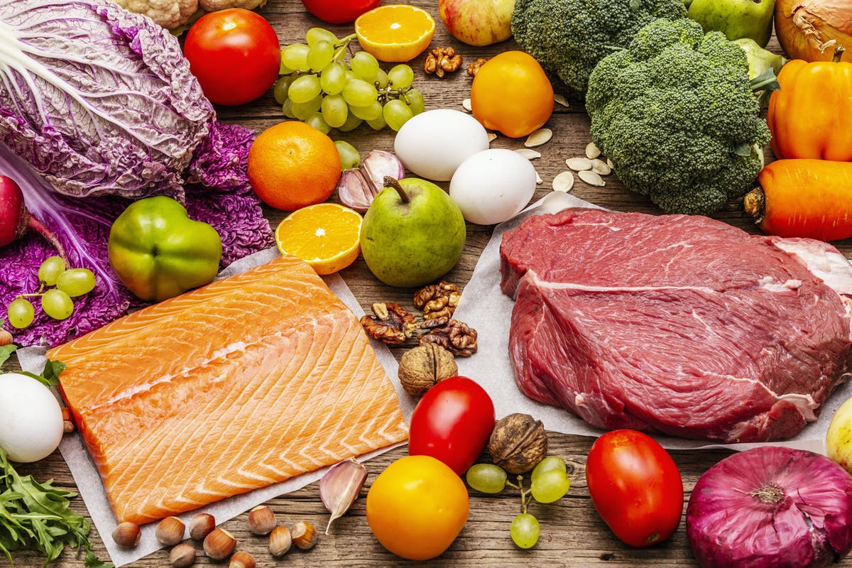 Trending paleo/pegan diet. Healthy balanced food concept. Set of fresh products, raw meat, salmon, vegetables and fruits. Old wooden boards background