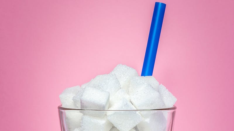 Glass full of sugar cubes – unhealthy diet concept.