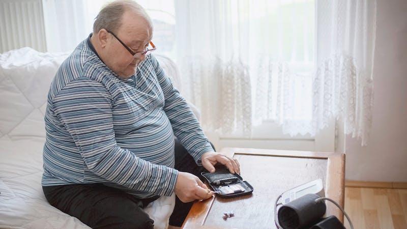Senior man checking blood sugar levels