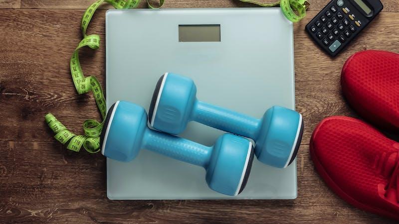 Fitness, slimming, diet concept. Calorie Counting. Floor weights, sneakers, dumbbells, calculator, measuring tape on wooden floor. Top view