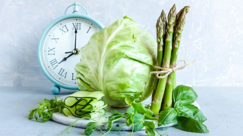 Alarm clock, Asparagus, microgreens, cucumber and cabbage – fresh green vegetables. Ketogenic diet, intermittent fasting, weight loss