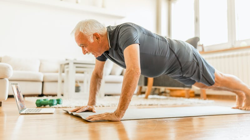 Active senior man home exercising with online coach