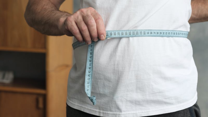 Man measuring his belly with measurement tape standing in the living room.