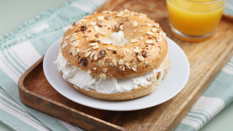 Breakfast with soft cheese bagel sandwich and a cup of orange juice