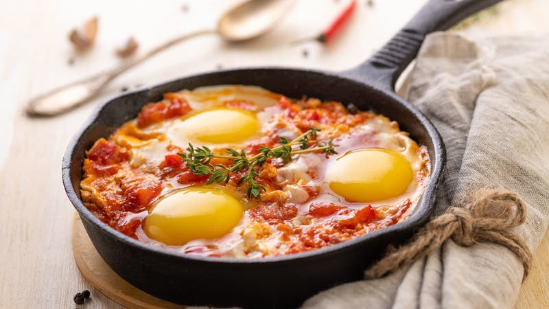 Shakshuka. Fried eggs with tomatoes and sweet pepper and herbs in a serving cast-iron frying pan.