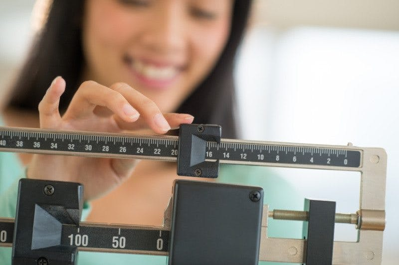 Midsection Of Woman Smiling While Adjusting Weight Scale