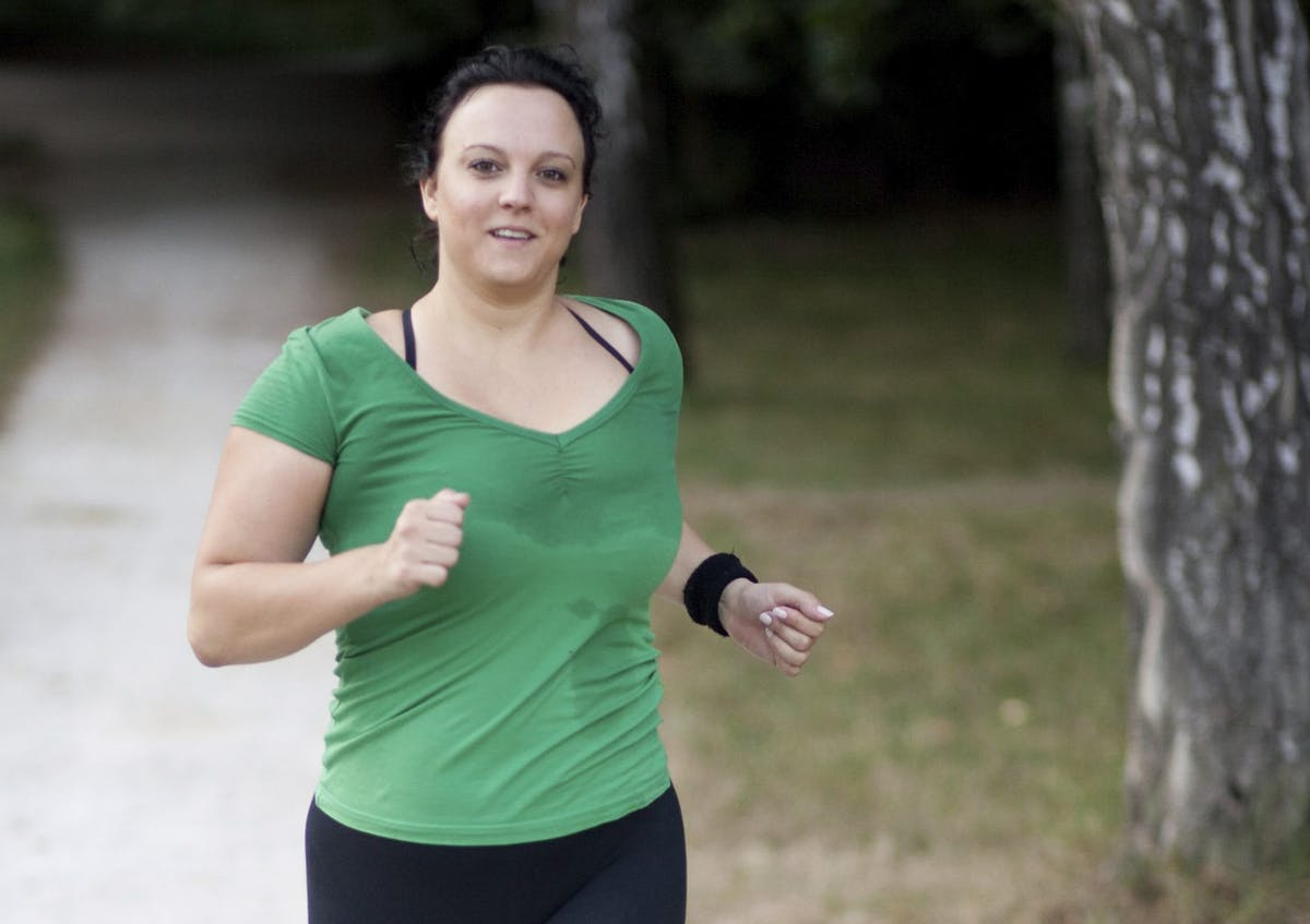 Overweight woman jogging in a park / forrest