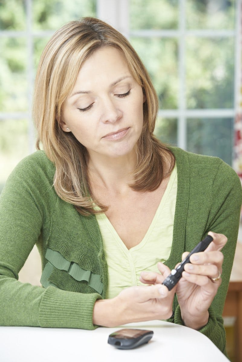 Woman Checking Blood Sugar Level At Home