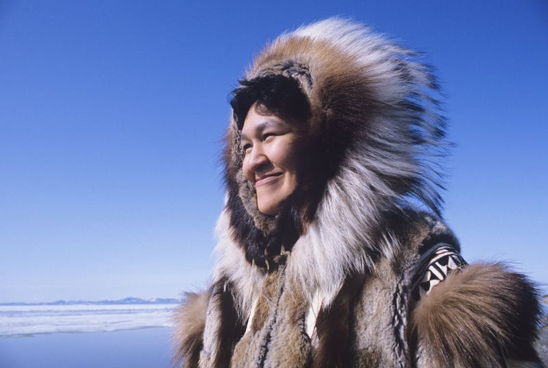 Smiling Eskimo woman wearing traditional clothing in wind against clear blue sky
