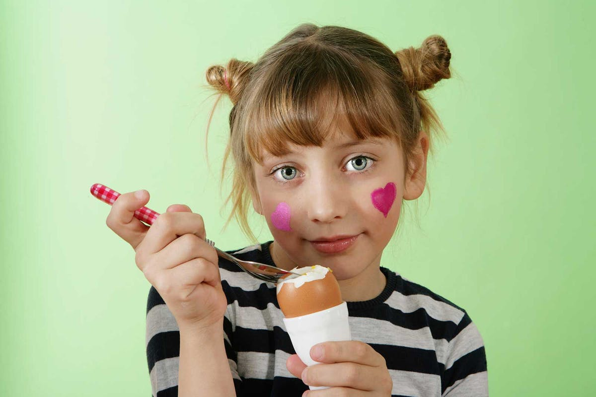 Kid eating an egg
