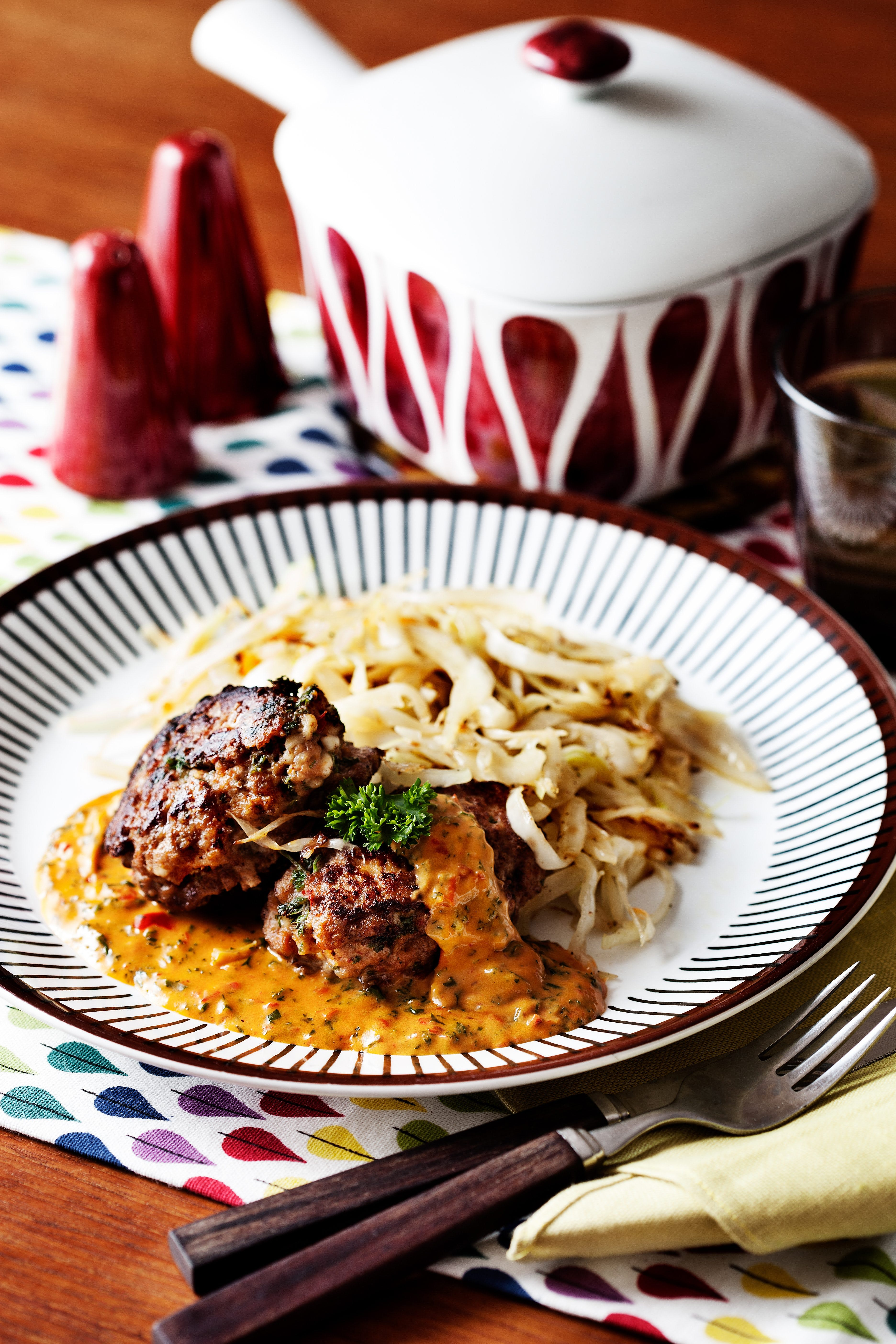 Keto hamburger patties with creamy tomato sauce and fried cabbage