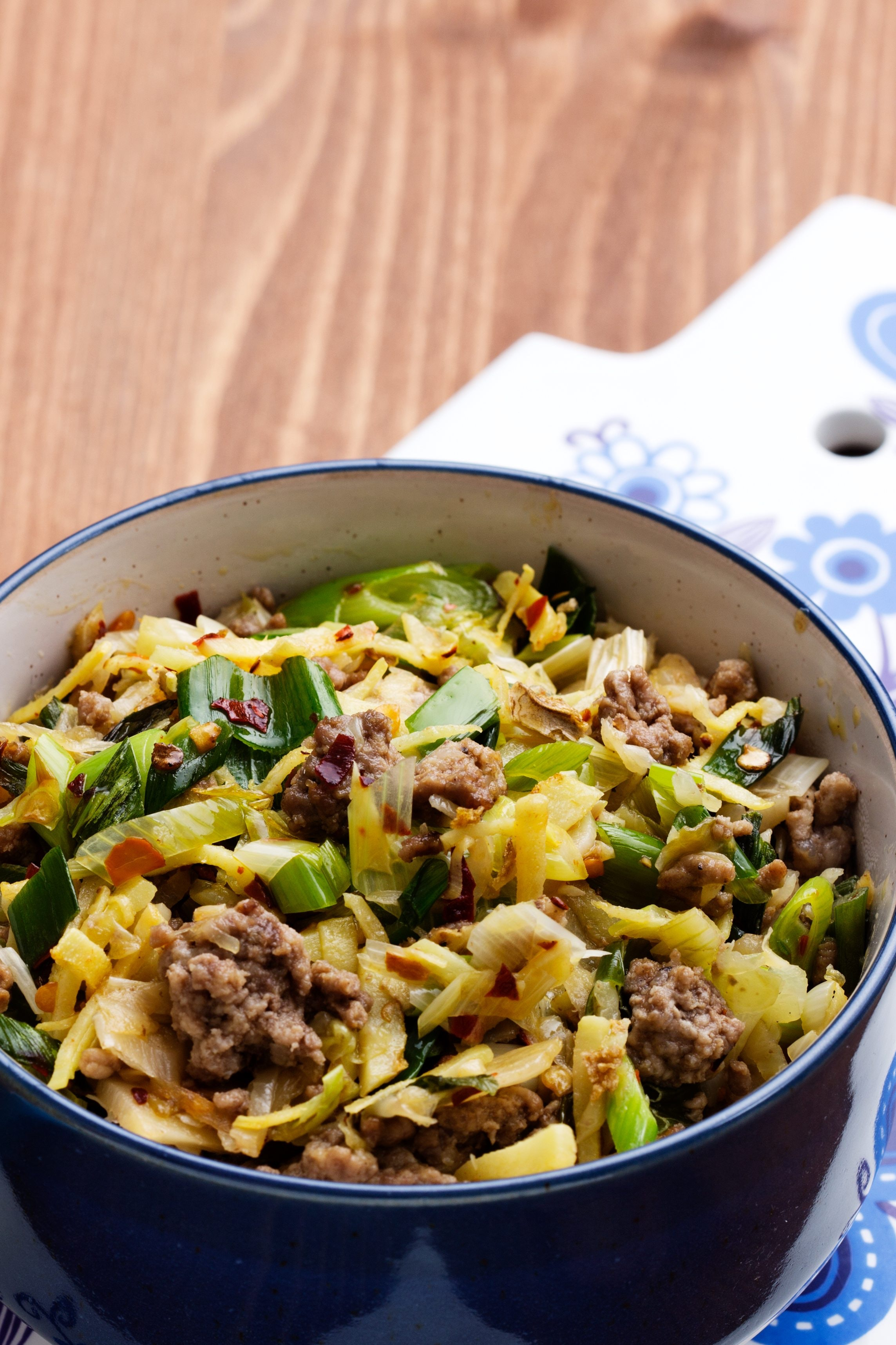 How to extinguish cabbage in a frying pan with meat, mushrooms, sausages