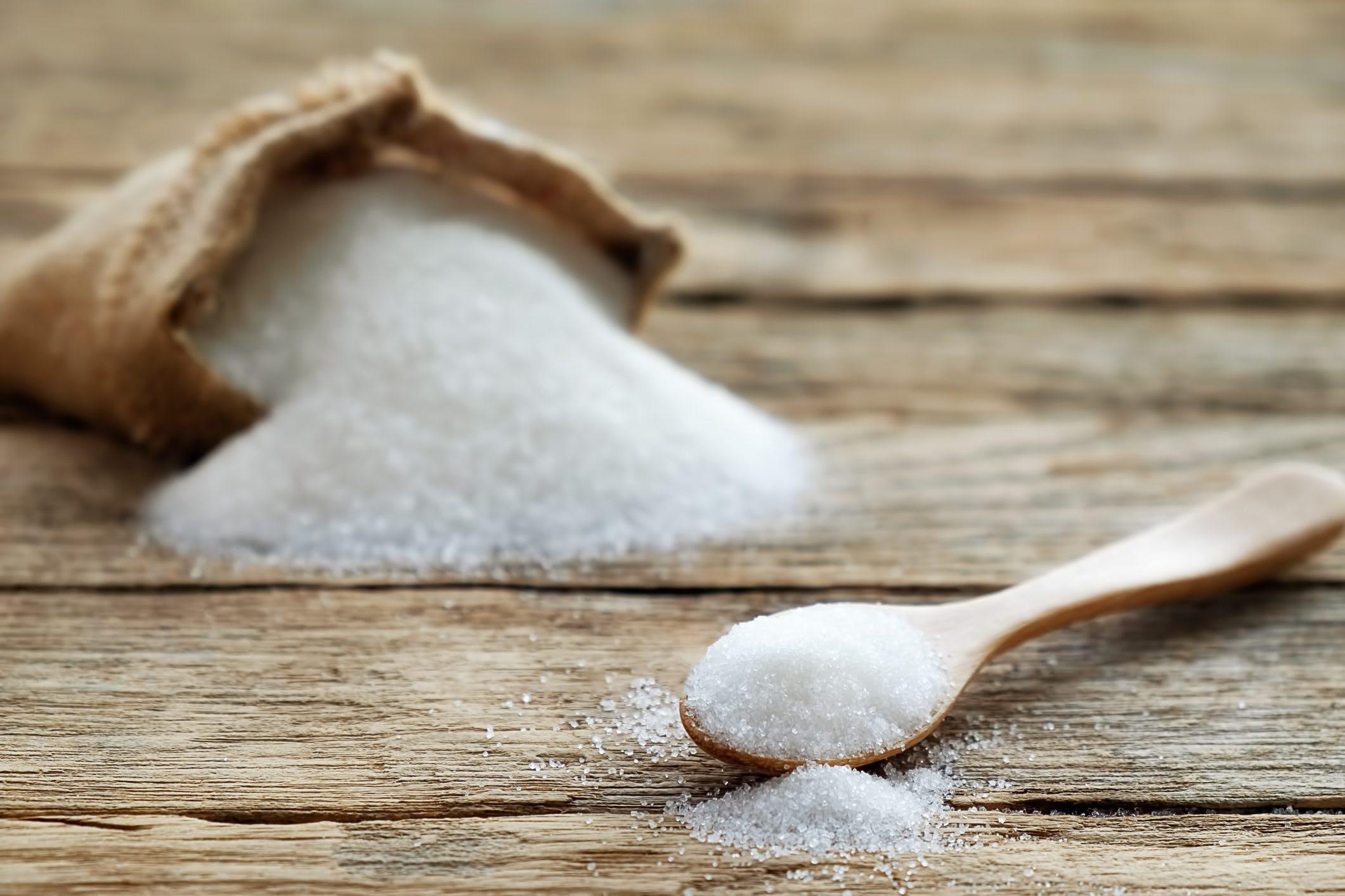 Sugar in burlap sack with sugarcane