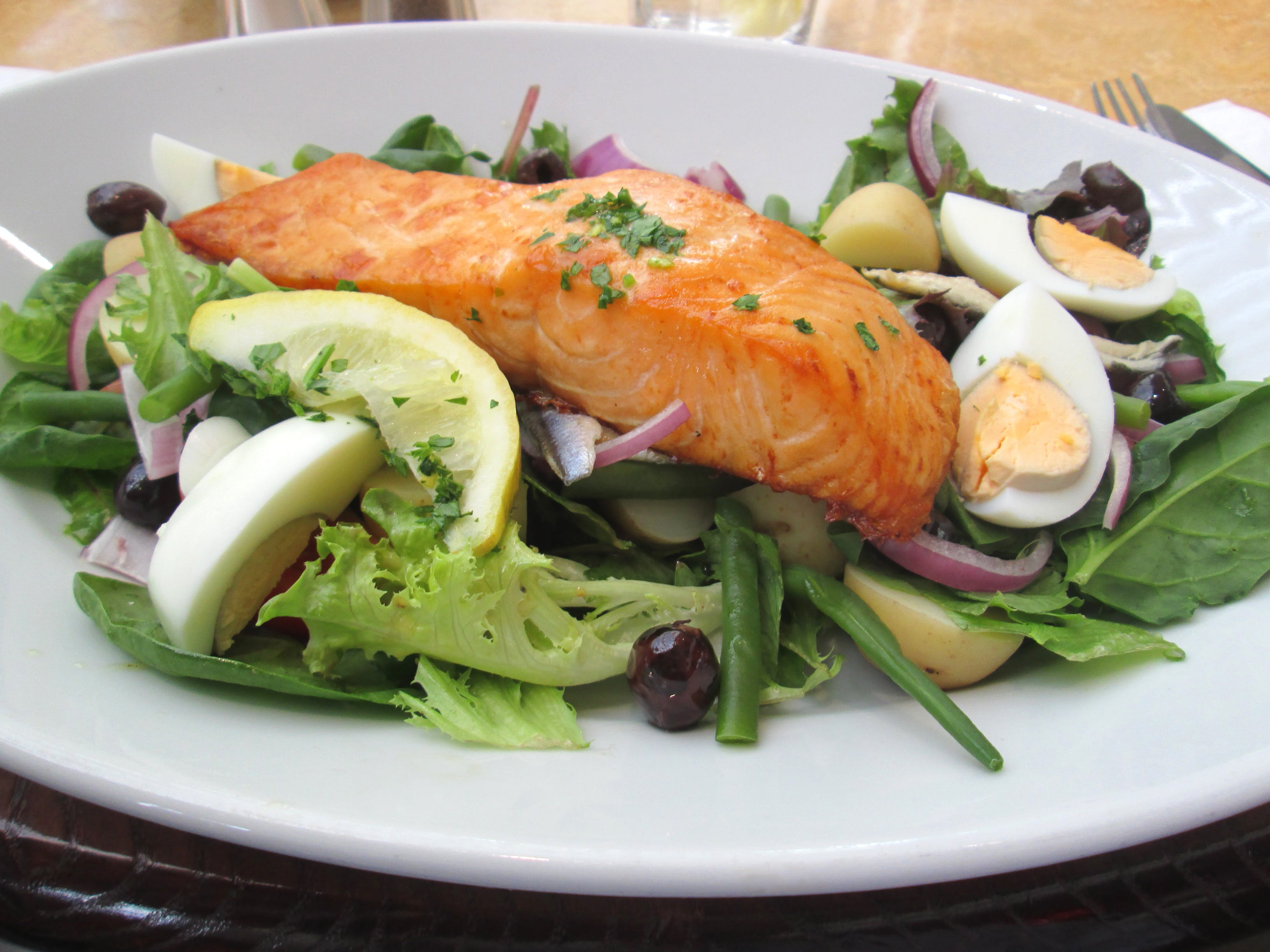 Image of pan fried salmon nicoise dish, salad, eggs, lemon