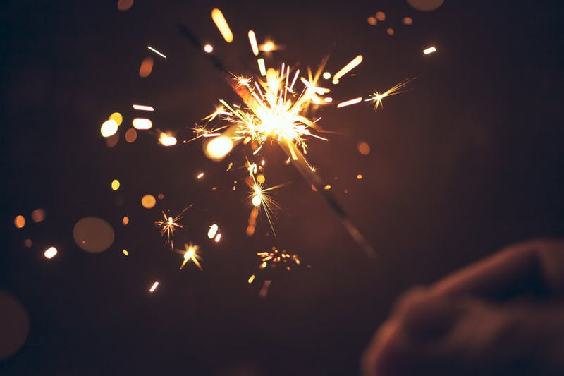 Person celebrating at night by holding sparkler – New Year Christmas Celebration