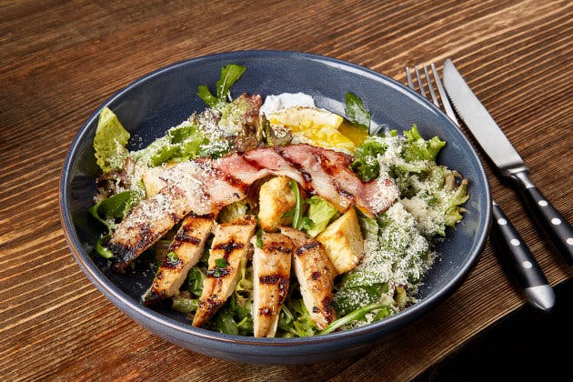 Chicken Salad. Chicken Caesar Salad. Caesar Salad with grilled chicken on plate. Grilled chicken breasts and fresh salad in plate