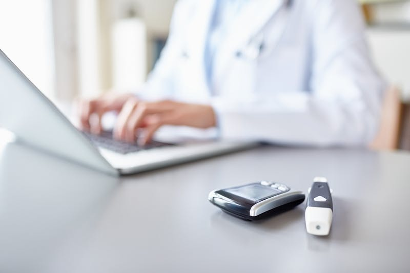 Glucometers on desk with doctor using laptop in background