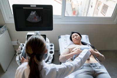 Asian woman lying down while female doctor is doing an ultrasound on her stomach