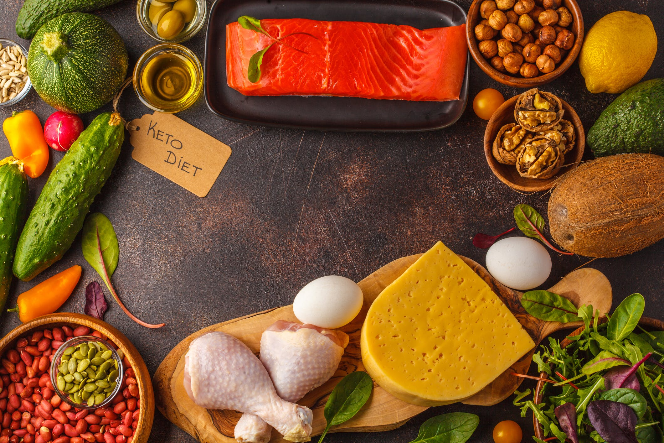 Keto (ketogenic) diet concept. High protein food, food frame background. Vegetables, fish, meat, cheese, nuts on a dark background.