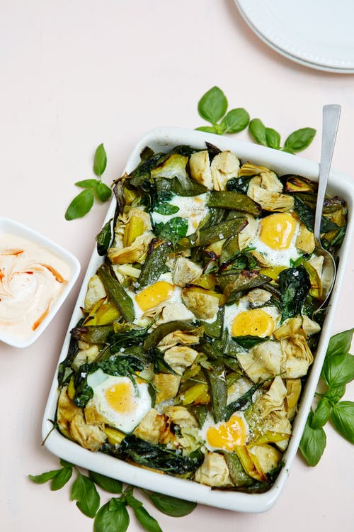 Baked eggs with veggies and hot yogurt sauce