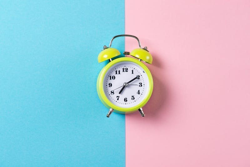 Green alarm clock with bells on blue and pink background, top view with copy space