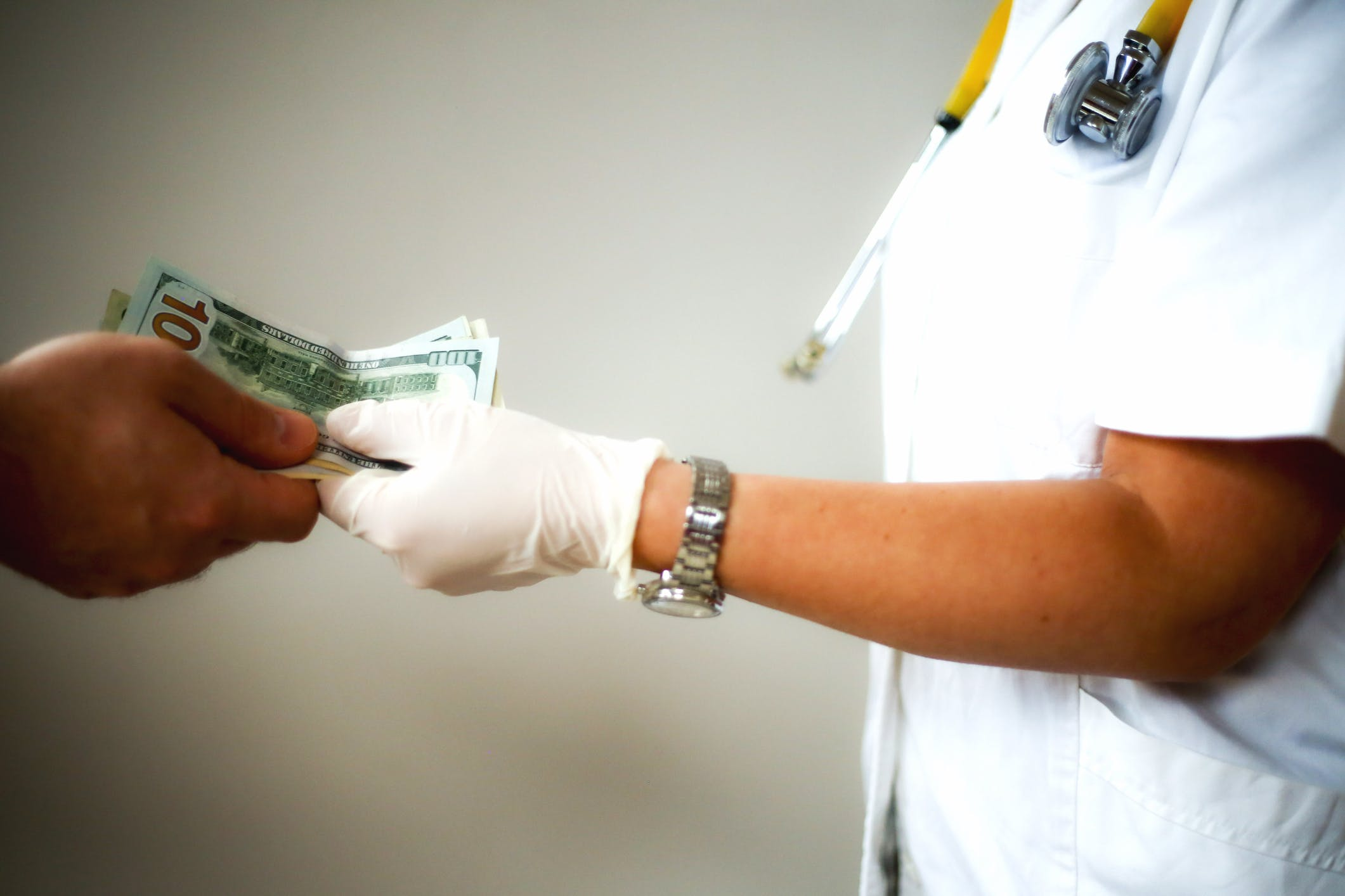 Doctor in white coat with stethoskop is offered money