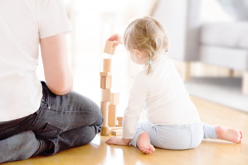 Cute girl playing with wooden blocks ont he floor with her father