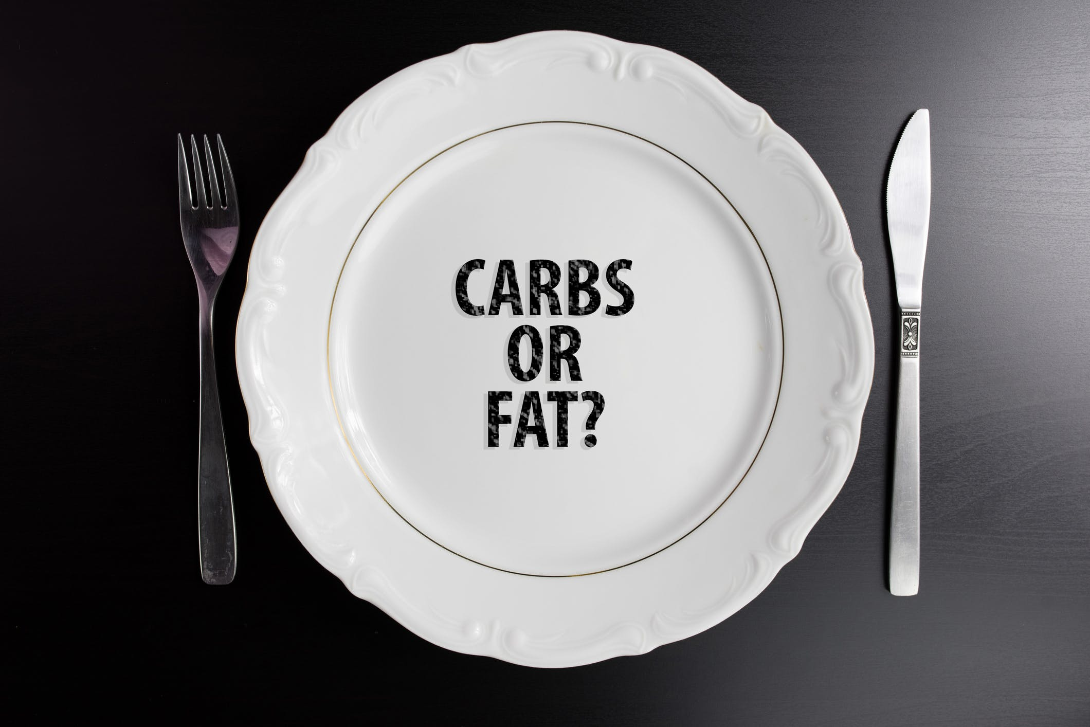 Carbs or fat concept Background for blog or webpage. Top view Plate with message. copy space for text.