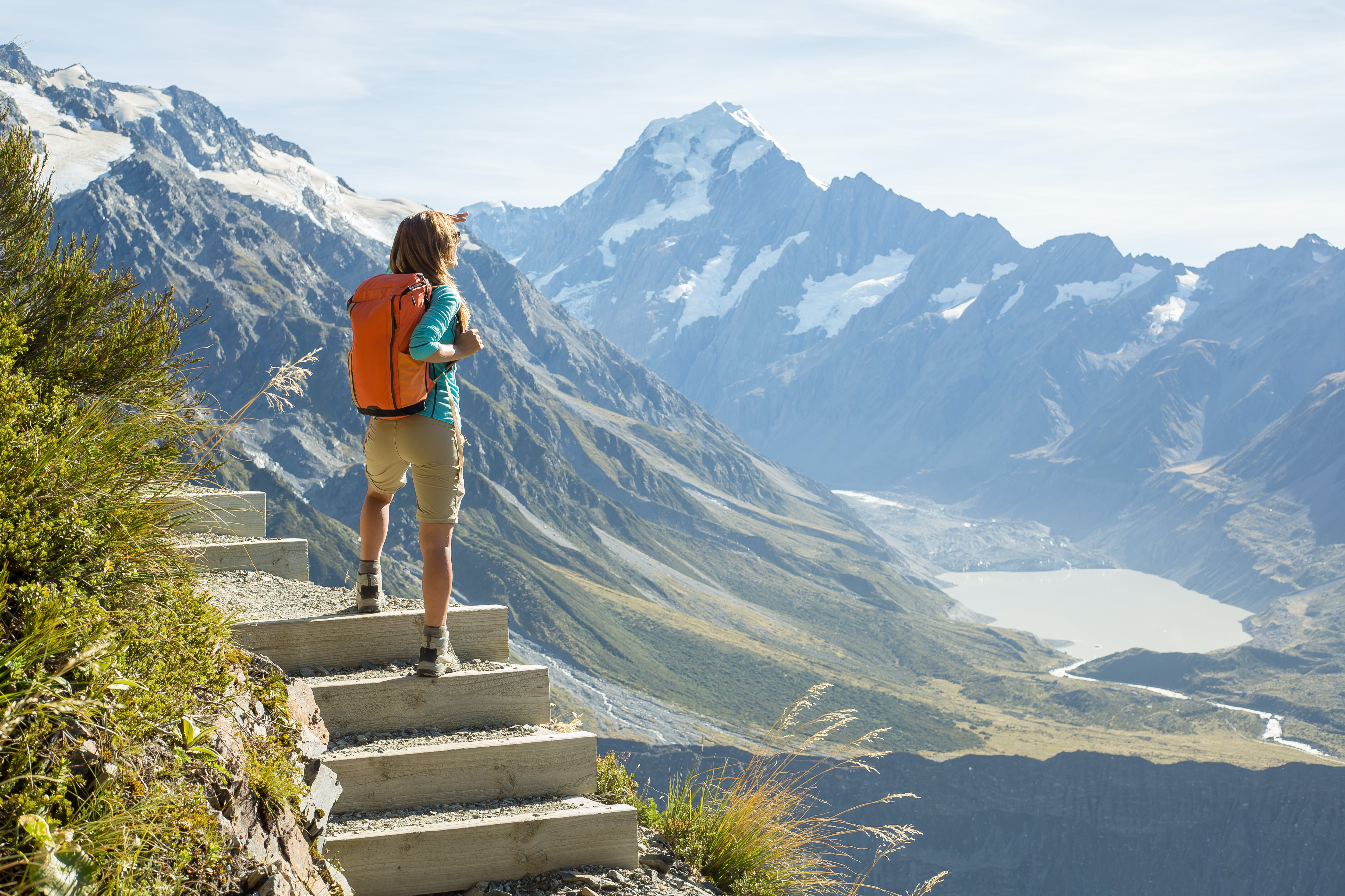 Hiker stands on a mountain top and admires view