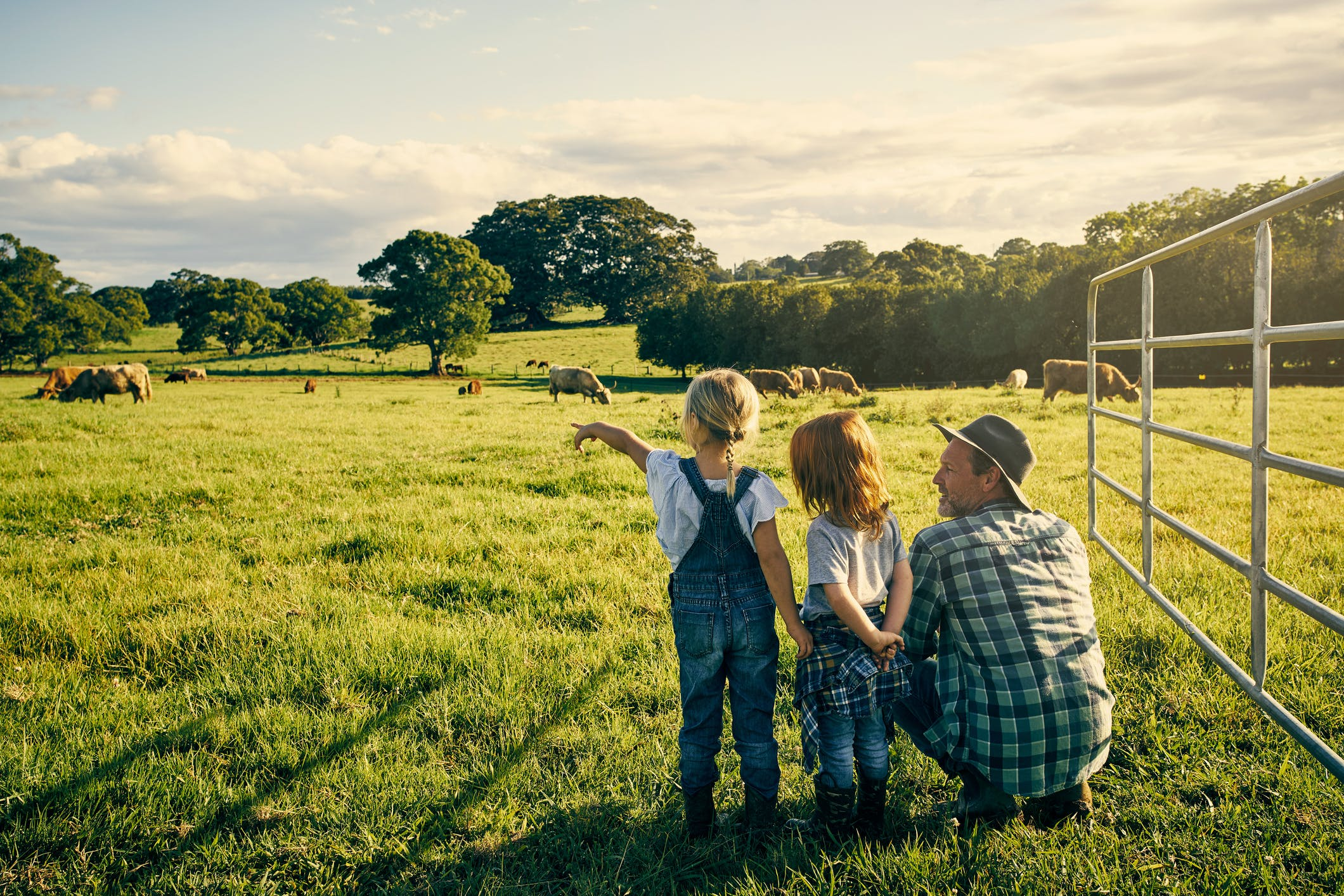 male farmer and his two kids on their farm
