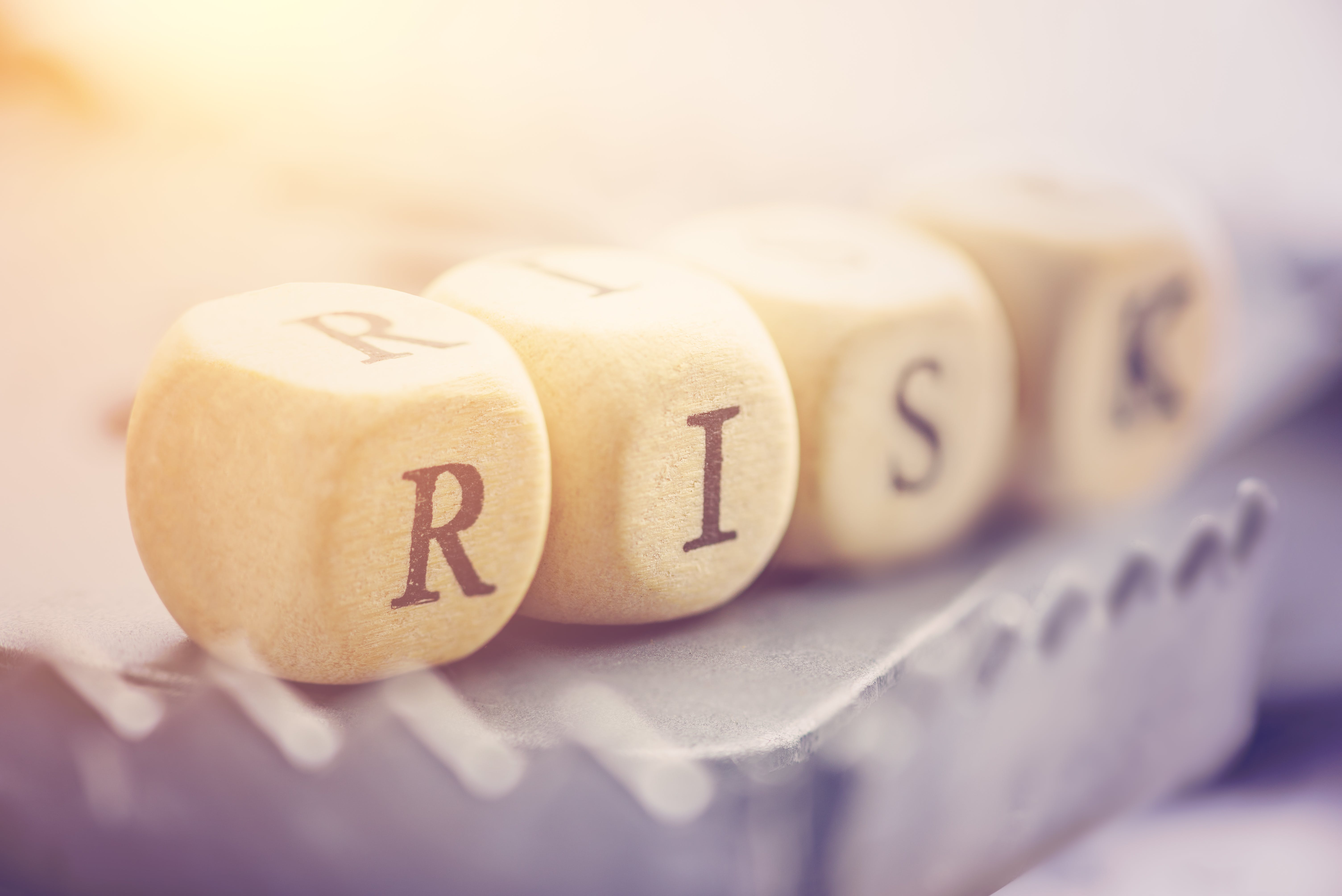 """Four dices are arranged in a word """"RISK"""" on a rat trap. Risk involves the chance an investment's actual return will differ from expected return, includes possibility of losing of original investment."""