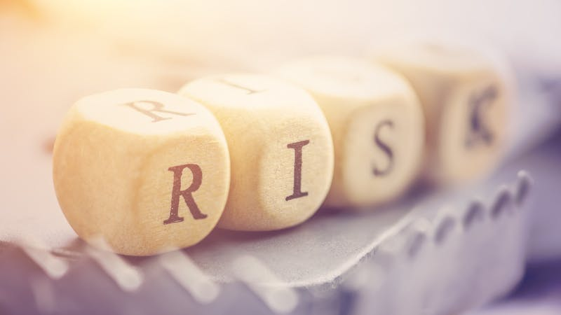 "Four dices are arranged in a word ""RISK"" on a rat trap. Risk involves the chance an investment's actual return will differ from expected return, includes possibility of losing of original investment."