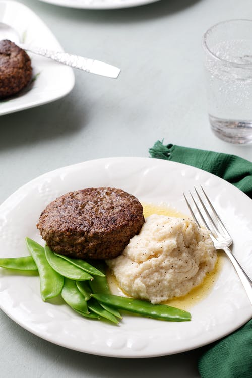 Veal burger with celery root mash and sugar snaps