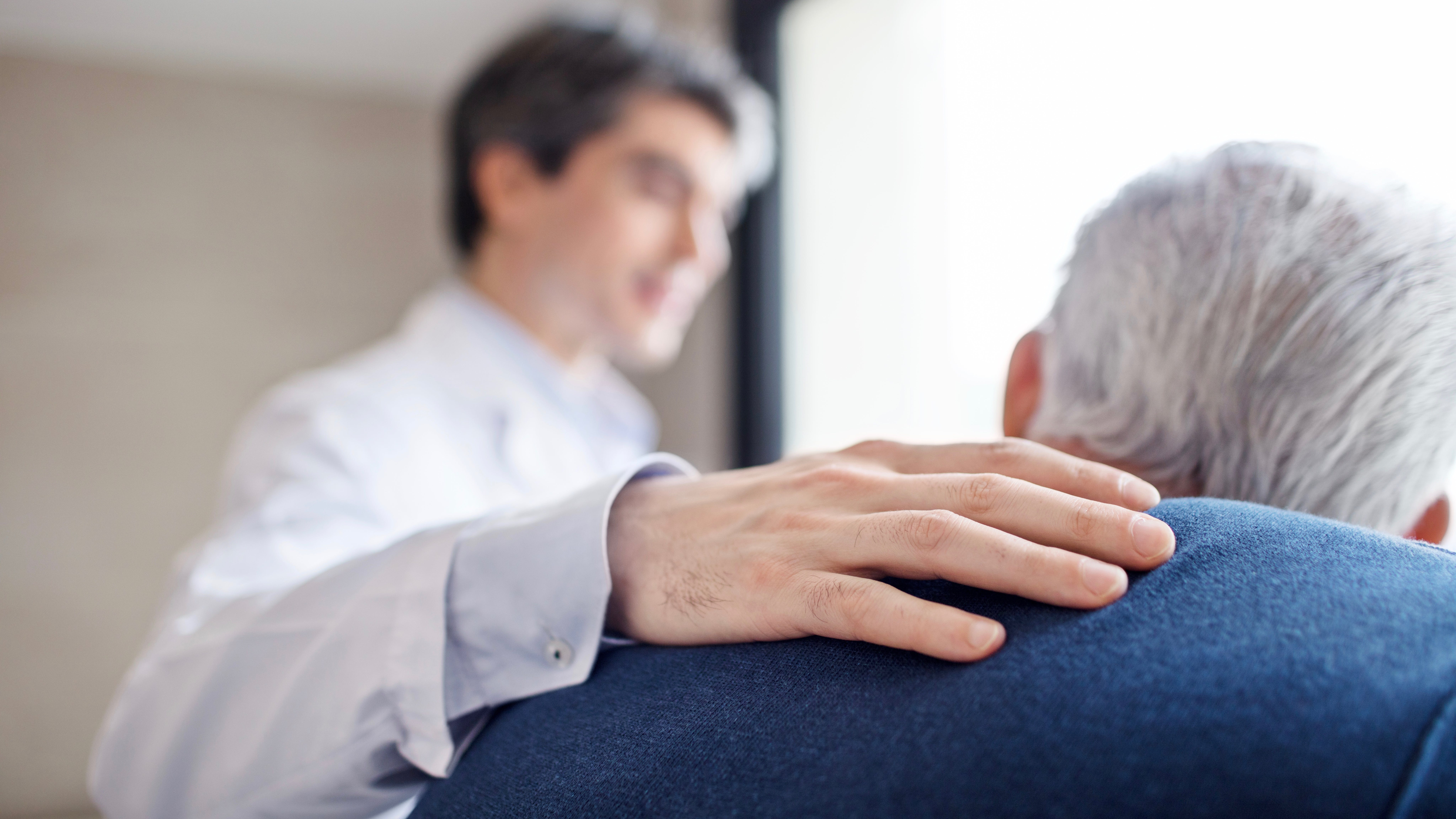 Doctor keeping hand on senior man's back