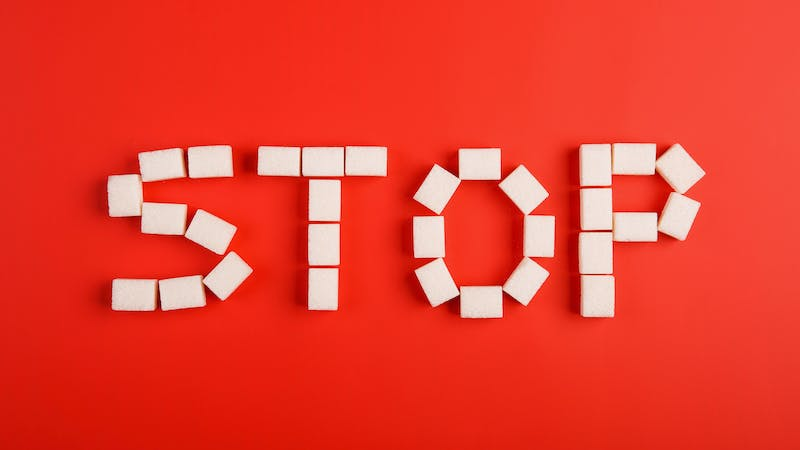 stop text from sugar cubes on red background