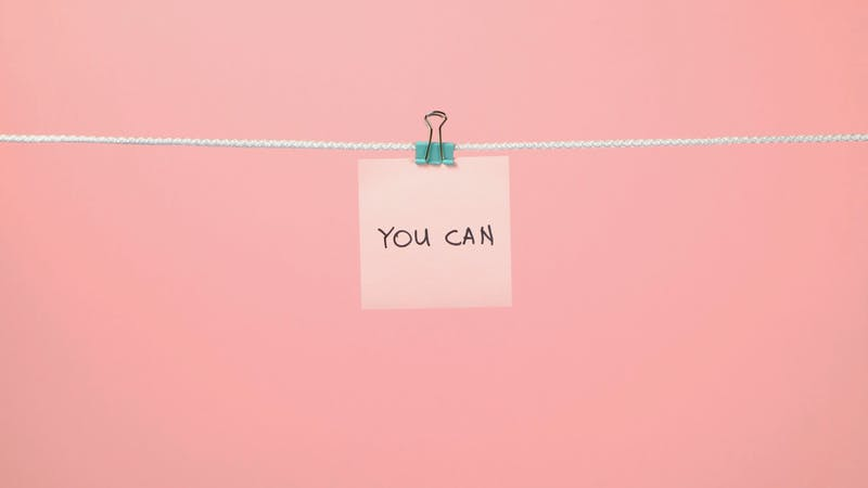 Pink paper sheet on the string with text You Can over colorful background