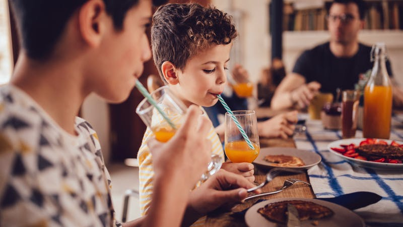 Boys drinking fresh orange juice during breakfast with family