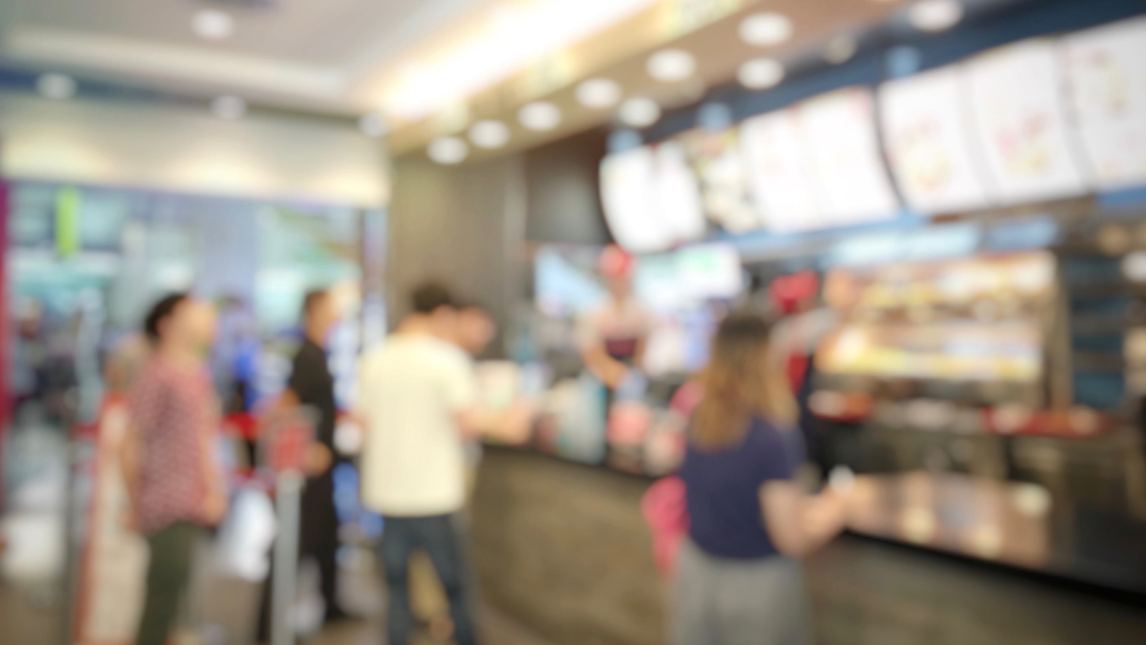 blurred abstract image of people standing for wait to order some food and make payment in fast food restaurant. Use as background image. vintage tone color and light effect.