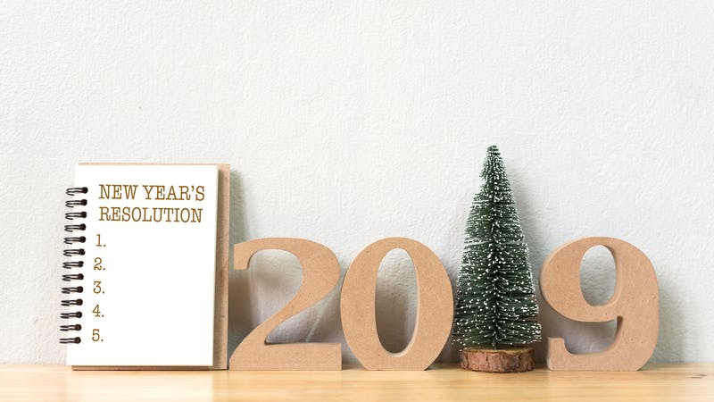 New year's resolution on a notebook and wood number 2019 with christmas tree on wood table and copy space