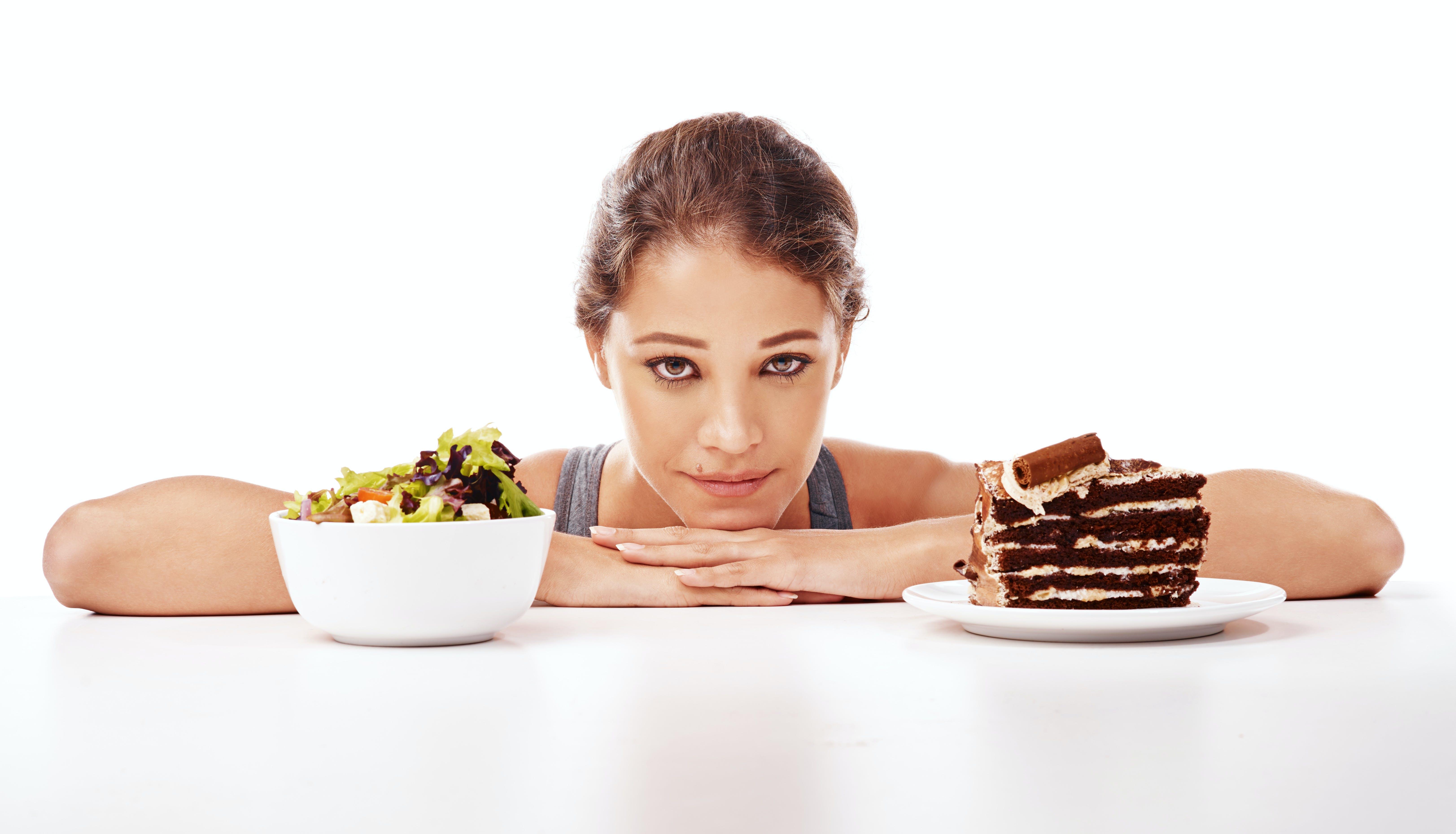 Woman-choosing-between-salad-or-chocolate-cake