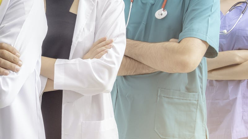 Doctors and nurses with uniform and stethoscope coordinate hands.
