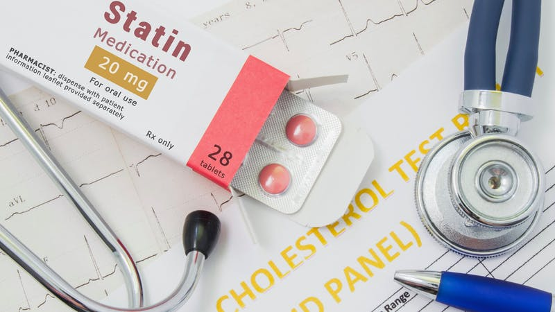 "Effects and treatment of statins concept photo. Open packaging with drugs tablets, on which is written ""Statin Medication"", lies near stethoscope, result analysis on cholesterol (lipid panel) and ECG"