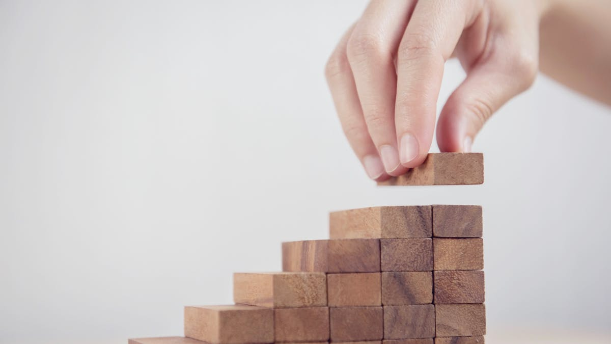Woman hand arranging wood block stacking as step stair. Business concept growth success process.