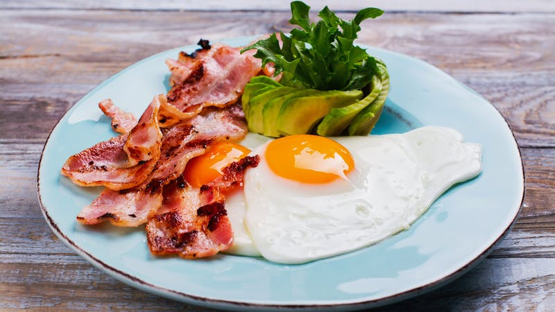 Continental breakfast with fried eggs, bacon and avokado